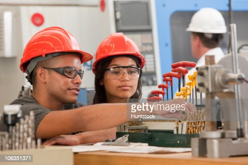 Engineering students selecting drill bits for a CNC machine : Stock Photo