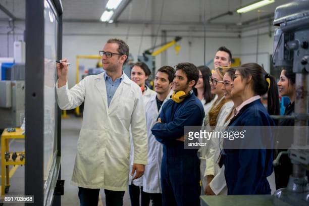 Engineering students with their teacher writing on the board