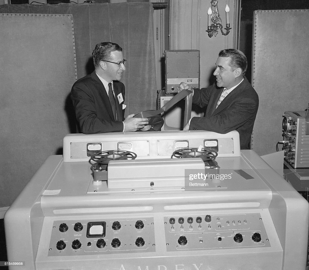 Engineering vice president of CBSTV William Lodge and George Long president of the Ampex Corporation here view a magnetic tape used to record...