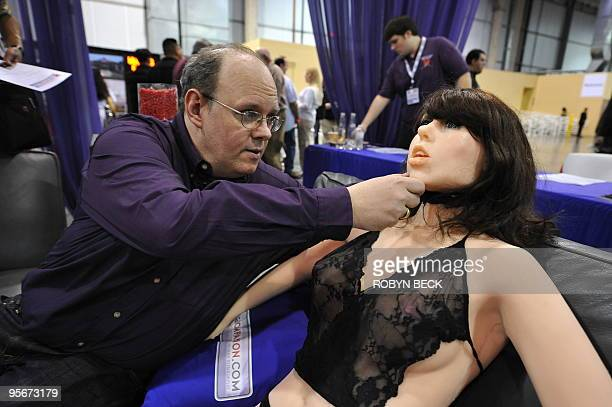 Engineerinventor Douglas Hines adjusts the head of his company's 'True Companion' sex robot Roxxxy at the TrueCompanioncom booth at the AVN Adult...