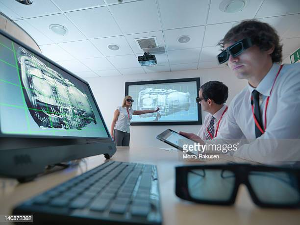 Engineers and apprentice in meeting room wearing 3D glasses to look at 3D screens