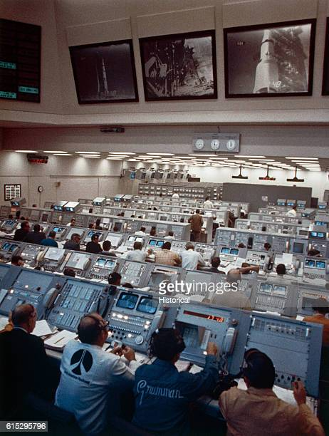 NASA engineers and technicians sit in long rows at computer consoles in a mission control room They face large screens that show various views of a...