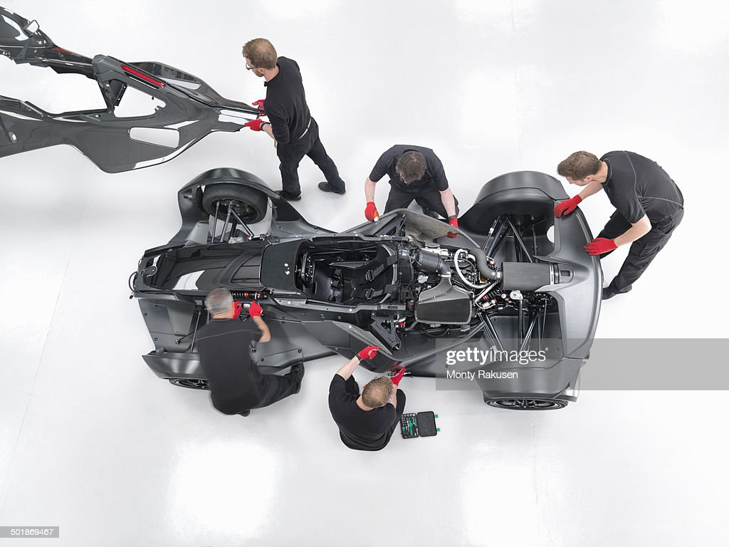 Engineers assemble supercar in sports car factory, overhead view