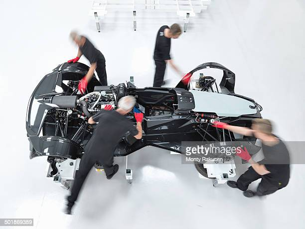 Engineers assembling supercar in sports car factory, overhead view