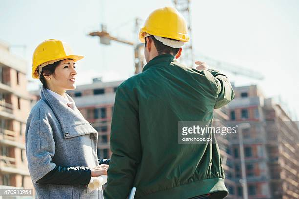 Engineers at construction site talking