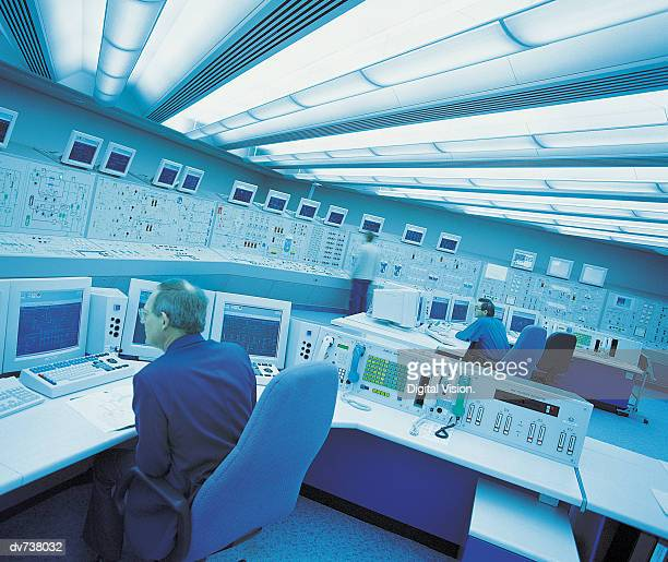 Engineers at control panel  in nuclear power station