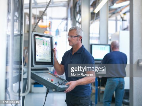 Engineers at lathe controls in factory
