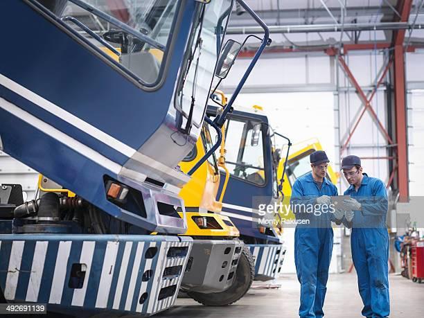 Engineers check details on digital tablet in truck repair factory