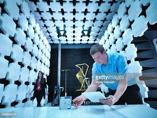 Engineers checking equipment under test (EUT), a continuous noise source in fully anechoic chamber with energy absorbers and bilog antenna