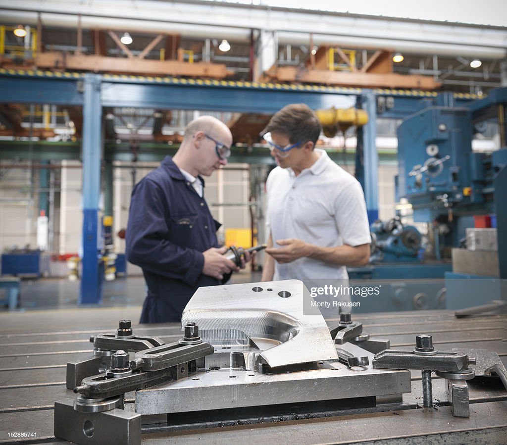 Engineers discussing car parts in car factory