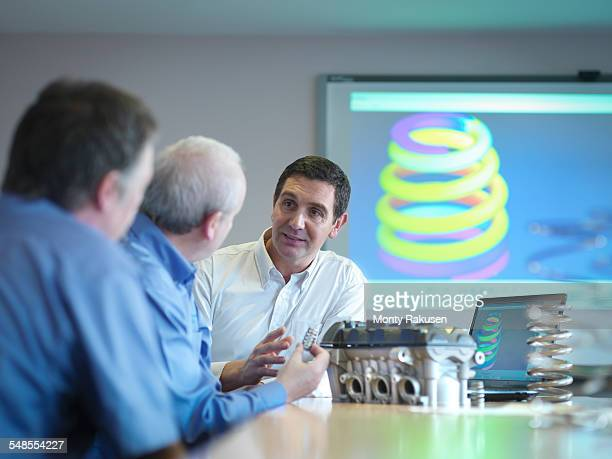 Engineers discussing engineering design in conference room