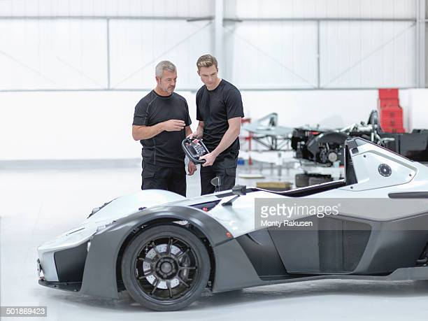 Engineers discussing supercar in sports car factory