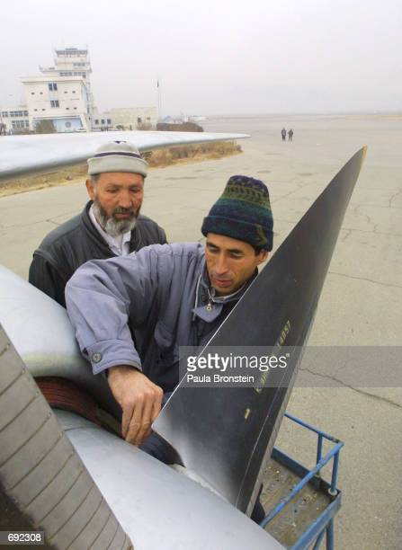 Engineers do maintenance on an Ariana Afghan Airlines plane on the tarmac at the Kabul airport January 10 2002 in Kabul Afghanistan The airport is in...