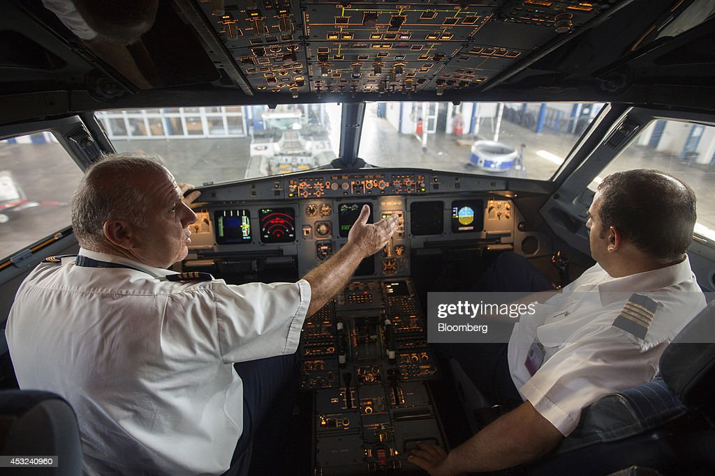 Engineers for Cyprus Airways Public Ltd conduct cockpit instrument checks inside an Airbus A320 aircraft manufactured by Airbus Group NV during...