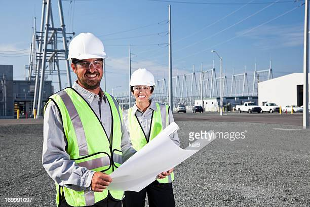 Engineers holding plans surveying power station