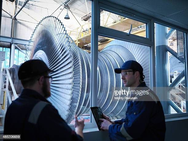 Engineers in front of viewing window in steam turbine repair works
