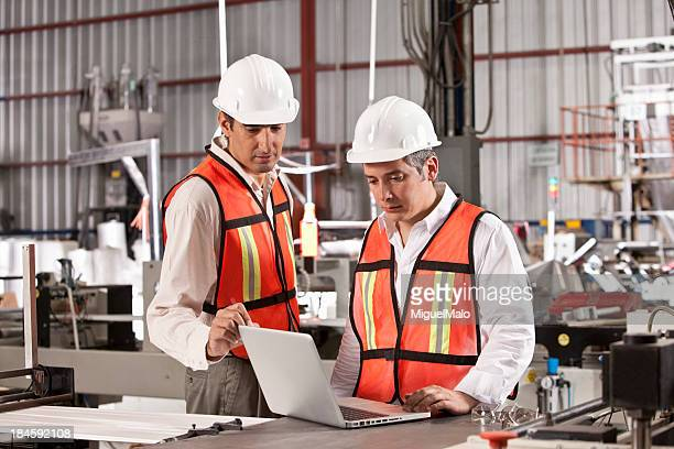 Engineers in outsourcing printing industry using a laptop