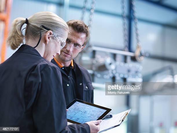 Engineers inspect plans on digital tablet in engineering factory