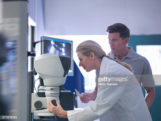 Engineers inspecting artificial hip joint parts using electron microscope in orthopaedic factory