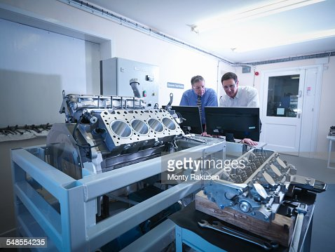 Engineers inspecting automotive engine in test facility