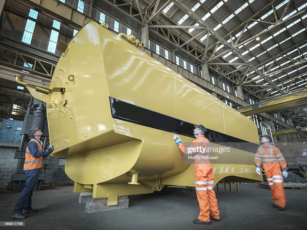 Engineers inspecting large tank in factory