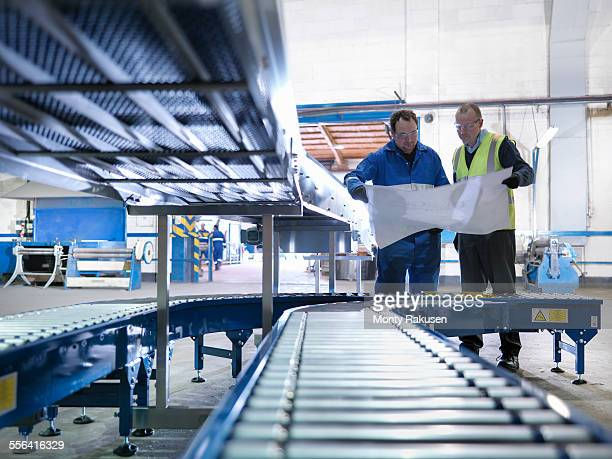 Engineers inspecting new conveyor in engineering factory