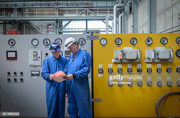 Engineers inspecting notes during power station outage