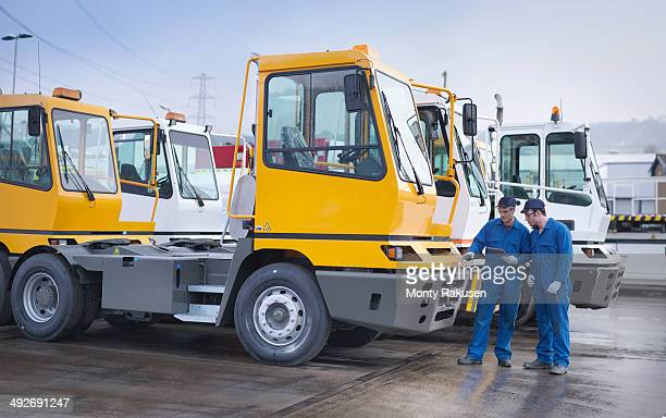Engineers inspecting parked trucks at truck repair factory