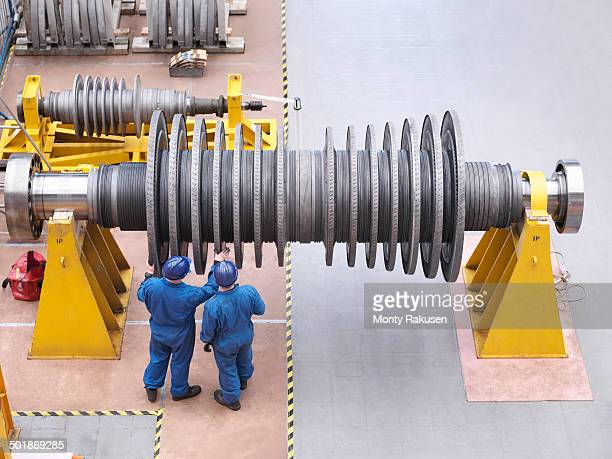 Engineers inspecting turbine during power station outage, high angle view