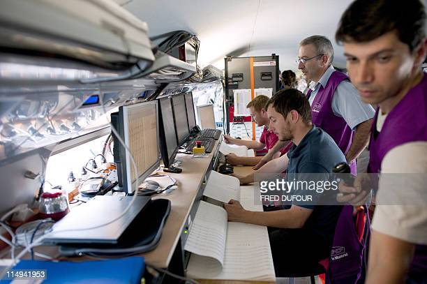 Engineers observe a train's performance on May 30 2011 during an official presentation of the new French engineering giant Alstom third generation...