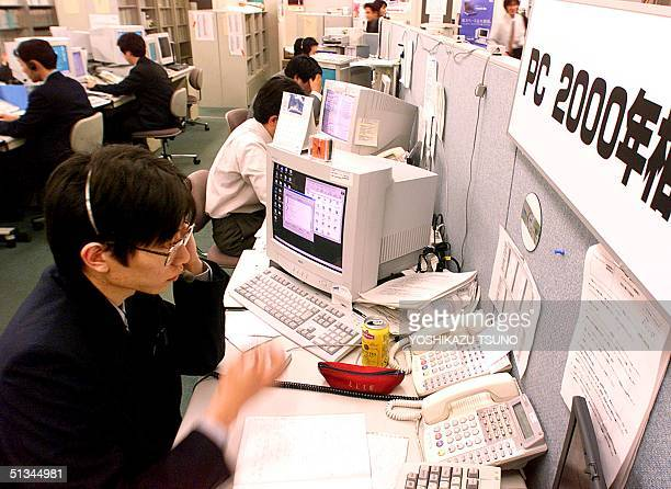 Engineers of Japan's electronics giant NEC are busy answering phone calls regarding their customers concerns with Y2K on the personal computers at...