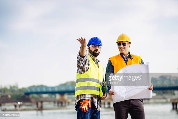 Engineers on bridge building site discussing next implementation phase