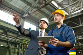 Waist up portrait of handsome businessman pointing up while discussing something with factory worker holding digital tablet, copy space