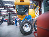 Engineers preparing to fix wheel in truck repair factory
