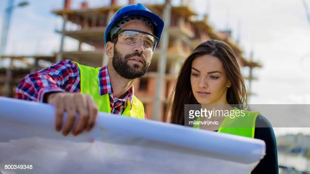 Engineers reading blue print at construction site