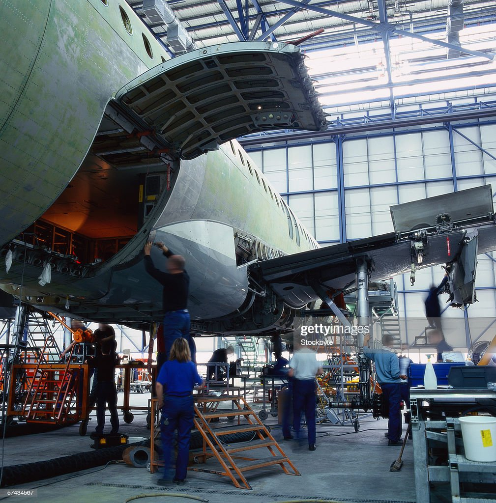 engineers repairing an aircraft in a hanger