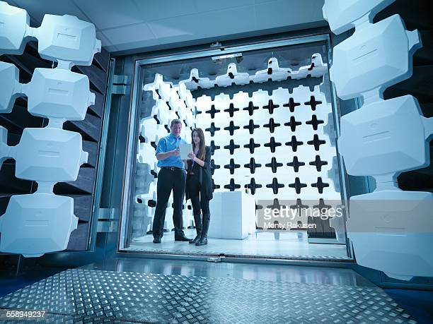 Engineers reviewing test results in laboratory in an anechoic chamber used for electromagnetic compatibility testing of electrical and electronic equipment