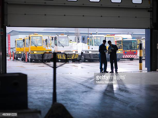 Engineers silhouetted in doorway in truck repair factory