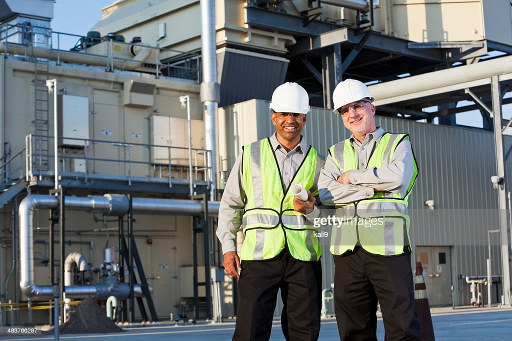 Engineers standing near power generator : Stock Photo