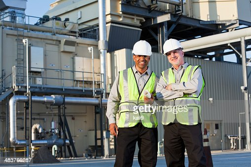 Engineers standing near power generator