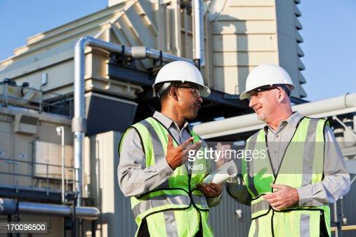 Engineers talking near power generator