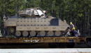 Engineers tie down a US Army Bradley light armor air defense and artillery vehicle after it was loaded onto a rail car January 11 2003 in Fort...