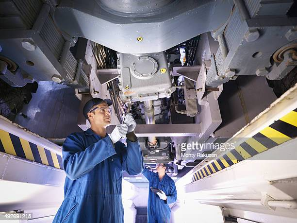 Engineers underneath truck in repair factory