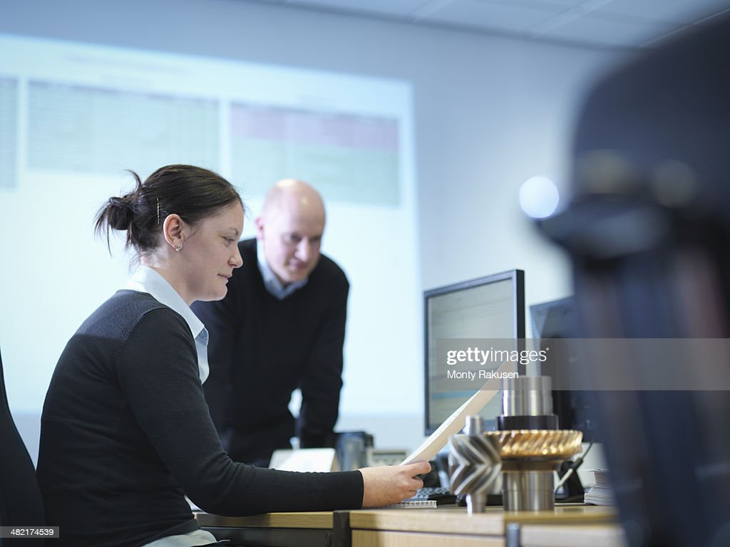 Engineers using computer aided design in factory office