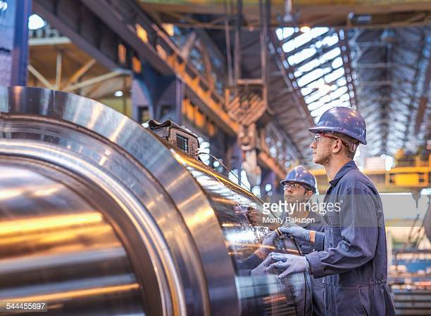 Engineers using ultrasound to check steel part in engineering factory