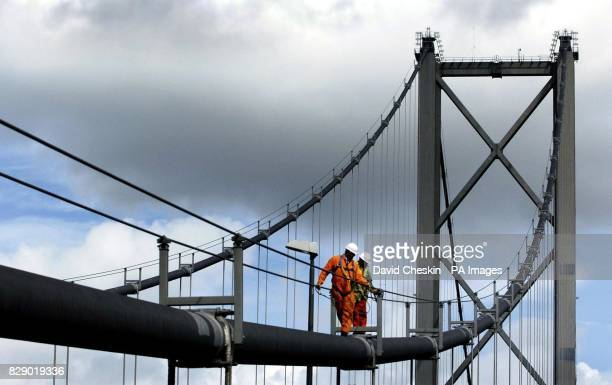 Engineers walks along one of the two foot diameter cables that cross the 3300 foot central span between the two main towers of the Forth Road Bridge...