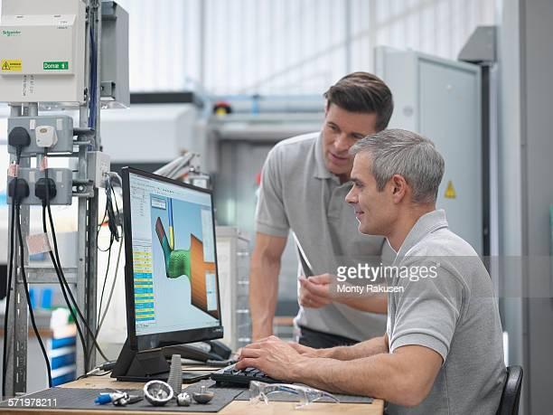 Engineers watching CNC lathe progress on screen in orthopaedic factory