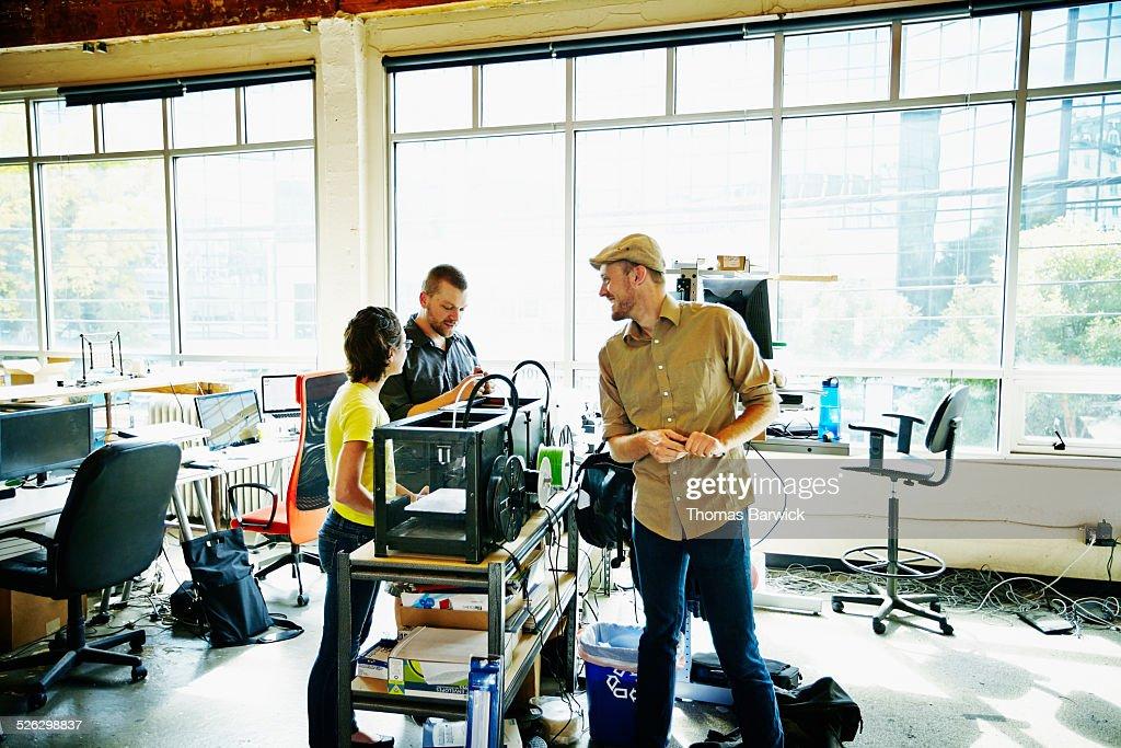 Smiling engineers watching prototype build on 3D printer in workshop