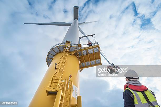 Engineers winch tools up wind turbine from boat at offshore windfarm, low angle view