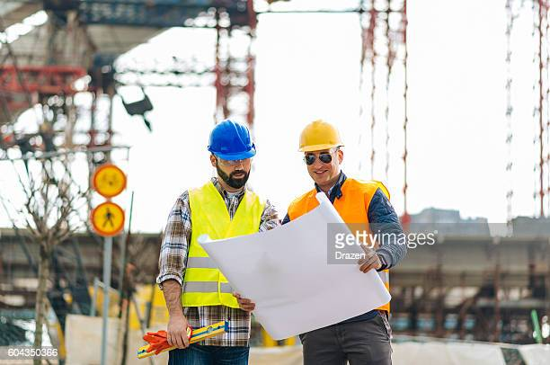 Engineers with blueprint on construction site